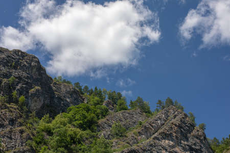 photograph of mountain peaks on a clear sunny day. white clouds in blue sky on a background. Stockfoto
