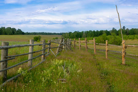 open space. wooden fences and green country field behind it. territory borders.