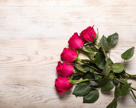 Bouquet of dark red roses on wood table background. Refinement of flowers. Pleasant and romantic gift for darling. Stockfoto