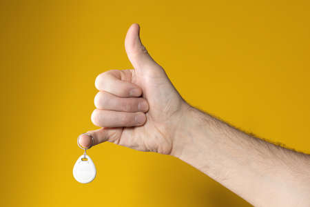 Man hand in form of raised thumb with hanging drop-shaped steel tag on little finger on yellow brown background. Successful in case. Everything is OK. Got what wanted.