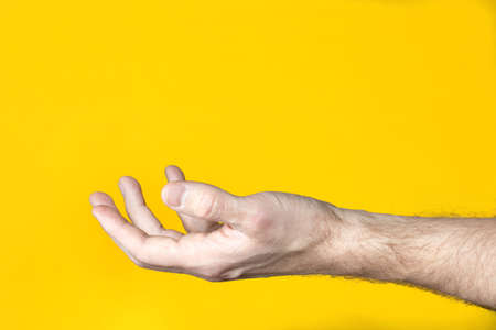 Man hand holding or taking something on yellow background.