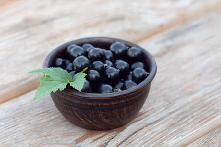 View of dark brown wooden bowl filled with black currant berries decorated with currant leaf on light wooden background. Table setting. Summer breakfast outside in country.