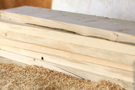 Selective focus of stack of processed wood planks with shavings on blurred wall background. Repair construction of house or shed. Woodworking workshop or planing boards. Stockfoto