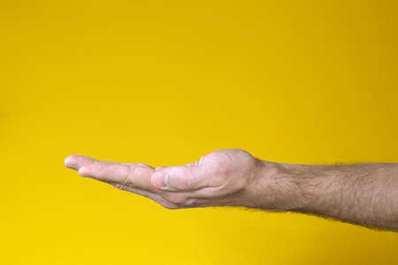 Man hand with palm facing up on yellow background. Gesture of asking or giving.