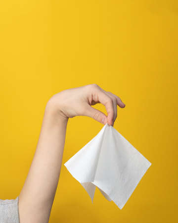 Close-up of hand gesture holding napkin neatly in middle with fingers on yellow background.  Hand disinfection or virus control. Way to throw away used napkin. Paper crafts or shadow theater.