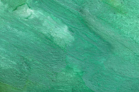 Beautiful bright rich emerald background of malachite stone surface. Rough uneven texture of green turquoise paint, finishing material or fabric.