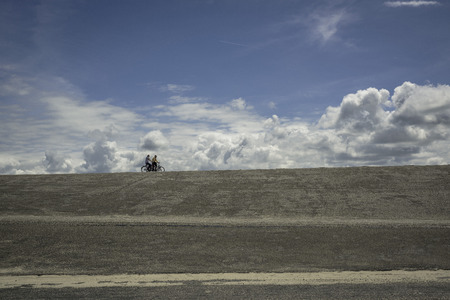 bicyclists: The Netherlands. - June 20, 2015: A couple of bicyclists moves on horizon under the clouds Editorial