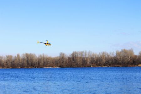 quickness: Yellow helicopter over the river Dnieper