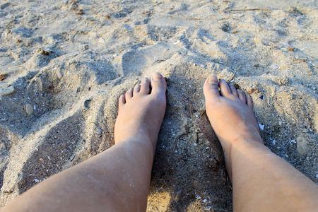 sandy feet: Female feet on sandy beach
