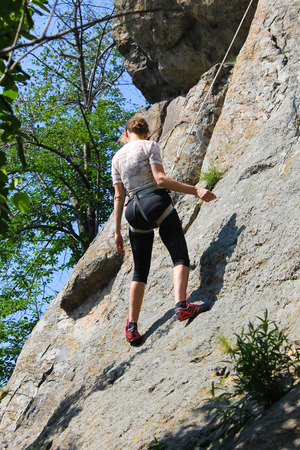 Woman rock climber climbs on a rock