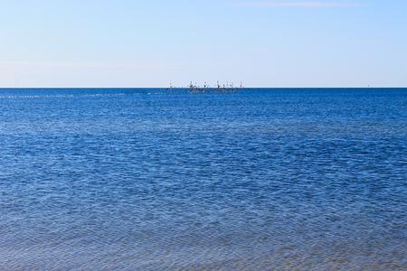 rickety: Seascape with fishing nets on horison Stock Photo