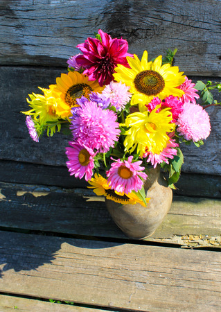 Autumn flowers in rustic clay jug on the wooden background