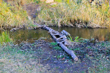 dodgy: Narrow old wooden bridge across small river Editorial