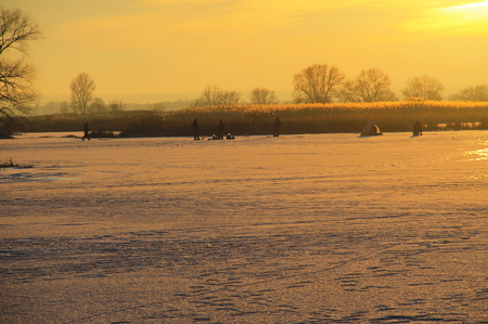 Winter fishing on the frozen river Dnieper at sunset Stock Photo
