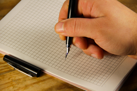 listings: Male hand writing using fountain pen on the notebook