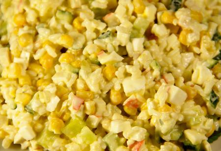 ensaladilla rusa: Close-up of salad with crab sticks corn cucumber eggs and rice Foto de archivo
