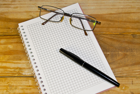 Notebook with glasses and fountain pen on the wooden desk