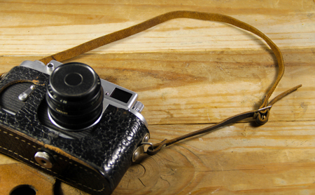 Old retro camera in leather case on the wooden background Stock Photo