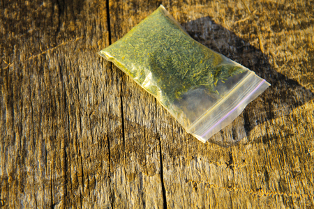 Marijuana in packet on the wooden background
