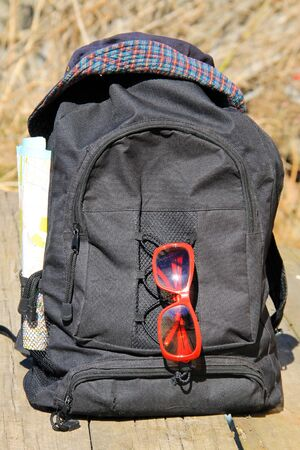 mapas conceptuales: Travel concept. Backpack with hat, red sunglasses and map Foto de archivo