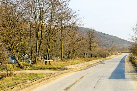 Asphalt road leading into the mountains on spring