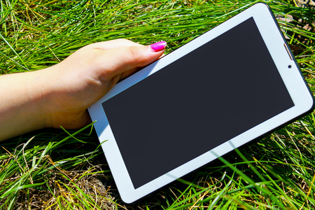 Womans hands holding white tablet with blank skreen on green grass