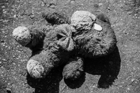 Abandoned dog doll on the pavement. Black-white tone Stock Photo