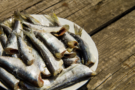 gutted: Gutted baltic herring on a plate on rustic wooden table