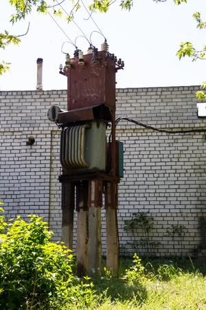 metal grid: Old electrical transformer. Device for distribution of supply of high-voltage energy Stock Photo