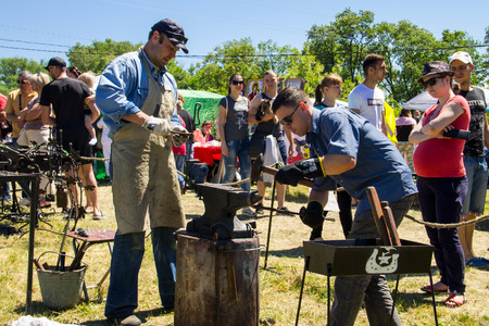 Kremenchug, Ukraine - June 3, 2017: Experienced blacksmith teaches the craft of a young man during festival
