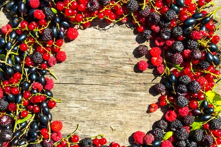 Summer frame with fresh colorful berries on wooden background. Blackberries, raspberries, red and black currant on table. Healthy eating and dieting concept