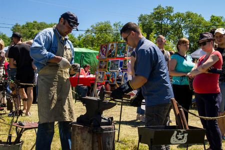 forge: Kremenchug, Ukraine - June 3, 2017: Experienced blacksmith teaches the craft of a young man during festival