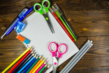 rubber sheet: Set of school stationery supplies. Blank notebook, colored pencils, pens, scissors, eraser on wooden desk. Back to school concept Stock Photo
