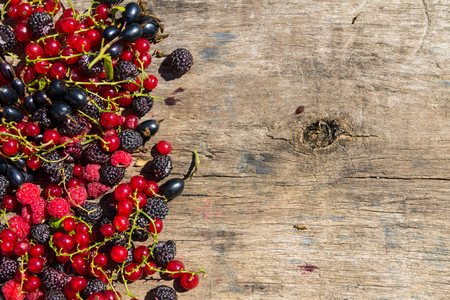 Fresh colorful berries on wooden background. Blackberries, raspberries, red and black currant on table. Healthy eating and dieting concept. Top view with copy space Stock Photo