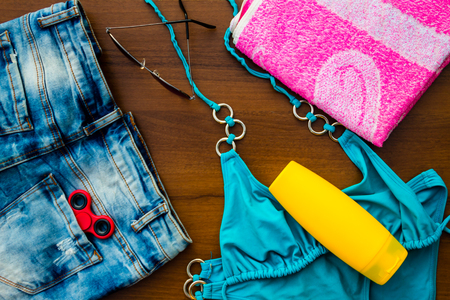 Set of beachwear on wooden background. Sunscreen, towel, blue bikini, sunglasses, jeans shorts and fidget spinner. Summer holiday concept