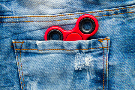 Red fidget spinner stress relieving toy in the pocket of blue jeans Stock Photo