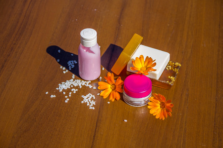 pot marigold: Beauty treatment products and calendula flowers on wooden background. Spa set Stock Photo