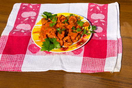 giblets cooked: Chicken gizzard stew in plate on rustic wooden table