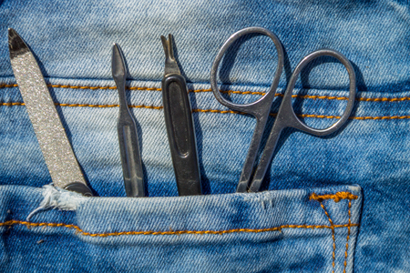 Basic set of manicure tools on jeans background. Nail and cuticle scissors, cuticle trimmer, nail file Stock Photo