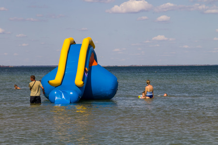the furlough: Genichesk, Ukraine - August 24, 2017: Inflatable water slide in Azov sea. Favorite vacation spot of children and adults Editorial