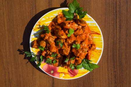 giblets cooked: Chicken gizzard stew in plate on the wooden table Stock Photo