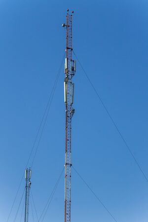 metal structure: Metal tower with antennas for mobile cell phone communications against blue sky Stock Photo
