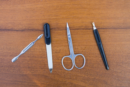 Basic set of manicure tools on wooden background. Nail and cuticle scissors, cuticle trimmer, nail file Stock Photo