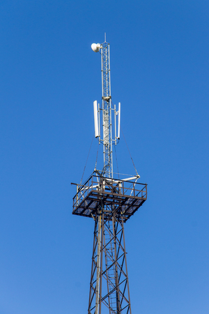 Metal tower with antennas for mobile cell phone communications against blue sky Stock Photo