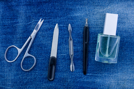 Basic set of manicure tools on jeans background. Nail and cuticle scissors, cuticle trimmer, nail file, nail polish