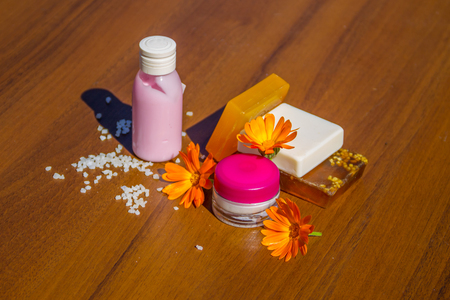 Beauty Treatment Products And Calendula Flowers On Wooden Background