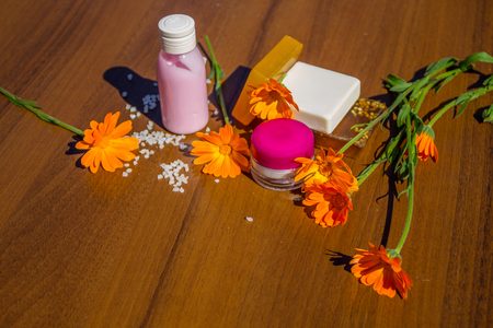 Beauty treatment products and calendula flowers on wooden background. Spa set Stock Photo