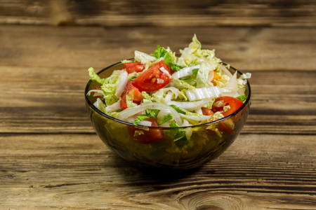 Fresh vegetable salad of chinese cabbage, tomato, pepper and onion with olive or sunflower oil on wooden table. Healthy food