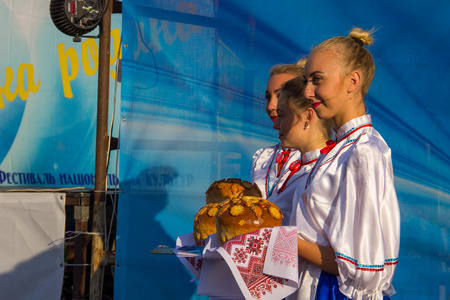 Genichesk, Ukraine - August 26, 2017: Traditional Slavic greeting. Girls in ukrainian national clothing with traditional loaf prepare to welcome guests of Festival of National Cultures Tavriyska rodyna (Tavria Family)