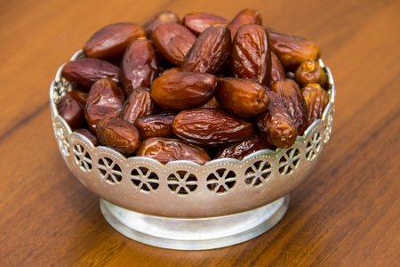 Dates fruit on a silver bowl on wooden table. The Muslim feast of the holy month of Ramadan Kareem